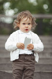 Little girl playing with mobile phone Stock Photography