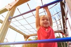 Little girl playing on monkey bars, kids sport Stock Image