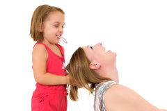 Little girl is playing with mother - fixing her hair. Royalty Free Stock Images