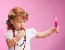 Little girl playing with mothers makeup Stock Photography