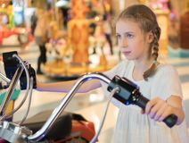 Little girl playing motorbike simulator game. Royalty Free Stock Images