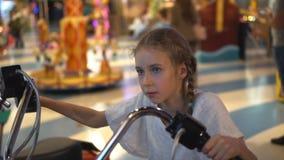 Little girl playing motorbike simulator. Little girl playing motorbike simulator game in theme park stock video