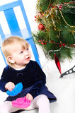 Little girl playing near the Christmas tree Stock Image
