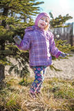 Little girl playing near a decorated pin tree Royalty Free Stock Photos