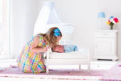 Little girl playing with newborn baby brother. Cute little girl kissing newborn brother. Toddler kid meeting new born sibling. Infant sleeping in toy bed in Royalty Free Stock Image