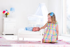 Little girl playing with newborn baby brother Royalty Free Stock Photography