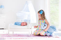 Little girl playing with newborn baby brother Stock Photography