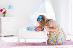 Little girl playing with newborn baby brother Royalty Free Stock Images