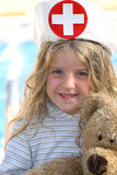 Little girl playing nurse with bear royalty free stock photo