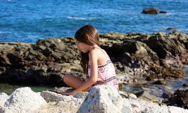 Little girl playing at ocean front in Los Cabos Mexico resort cliff sea royalty free stock photo