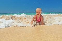 Little girl playing in ocean surf Royalty Free Stock Images