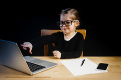 Little girl playing in the office with a computer Stock Photo