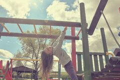 Free Little Girl Playing On Playground, Hanging Walk Along The Monkey Bars. Stock Images - 181772264