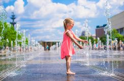 Little girl playing in open street fountain at hot Royalty Free Stock Images