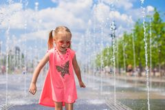 Little girl playing in open street fountain at hot Stock Photo