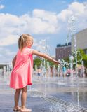 Little girl playing in open street fountain at hot Stock Photos