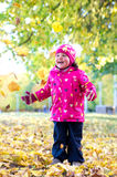 Little girl playing outdoors Stock Photos
