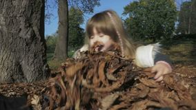 Little girl playing outdoors in autumn park. stock footage
