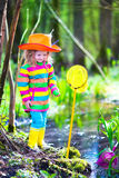Little girl playing outdoors catching a frog Royalty Free Stock Photos
