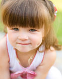 Little girl is playing outdoors. Little cheerful girl is playing outdoors Stock Image