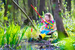 Little girl playing outdoors fishing Royalty Free Stock Images