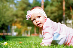Little girl playing outdoors in the park. Stock Photos