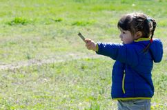 Little girl playing outdoors with a wooden stick Royalty Free Stock Image