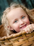 Little girl in the basket. Little girl is playing outside and hiding in the wooden basket Royalty Free Stock Photo