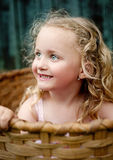 Little girl in the basket. Little girl is playing outside and hiding in the wooden basket Stock Photos