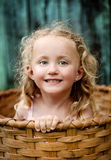 Little girl in the basket. Little girl is playing outside and hiding in the wooden basket Stock Photo