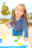 Little girl playing and painting Stock Image