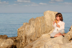 Little girl playing pan pipe. By the sea Royalty Free Stock Photos