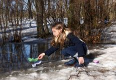 A little girl playing with paper boats in early spring semi-frozen puddles Stock Photography