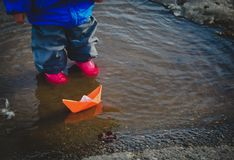 Little girl playing with paper boats in water puddle. Seasonal activities stock photography