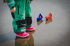Little girl playing with paper boats in water puddle. Seasonal activities stock photo