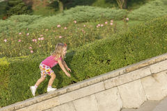 Little girl playing on parapet Royalty Free Stock Image