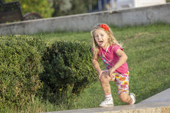 Little girl playing on parapet Royalty Free Stock Photo
