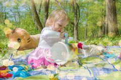 Little girl playing in the park with a bucket and crayons. On a sunny day Royalty Free Stock Photos