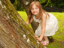 Little girl playing in park climbing to e tree. Royalty Free Stock Images