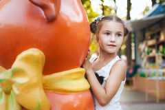 Little girl playing in the park. Little girl hides behind an orange statue Stock Photo