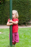 Little girl playing peek-a-boo. In the garden peering out from behind a green pole that she is hugging with one eye royalty free stock photo