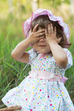 Little girl playing peek-a-boo Stock Images