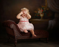 Little girl playing peek-a-boo. Portrait of little girl in pink Royalty Free Stock Photo