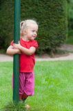 Little girl playing peek-a-boo. In the garden peering out from behind a green pole Stock Photo
