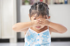 Little girl playing peekaboo or crying Stock Image