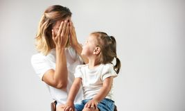 Little girl playing peekaboo game with her mother stock photography