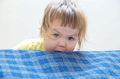 Little girl playing peeking from bed. Playful child portrait Stock Image