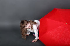 Little girl playing peeking from behind red umbrella. Little girl playing peeking from behind large red umbrella Stock Image
