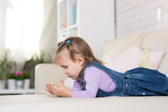 Little girl is playing with the phone Royalty Free Stock Image