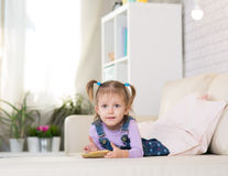 Little girl is playing with the phone Stock Image